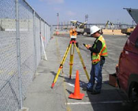 A surveyor using a tripod tool in front of a chain link fence