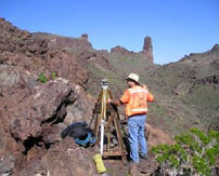 A surveyor using a tripod tool in the middle of a rocky hillside