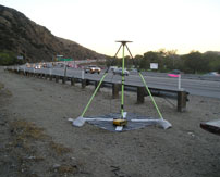 Tripod survey tool on the side of a freeway